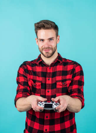 Everything is so real. young man hold game controller to play video games. relax at home. man play video games. console controller joystick. football or soccer game on TV. playing computer game Zdjęcie Seryjne