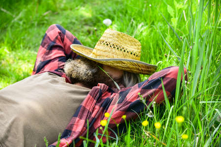 sweet dreams. ranch hipster wear checkered shirt. farming and agriculture. relaxed farmer in straw hat. mature man gardener relax on green grass. enjoy spring nature. summer season in perfect