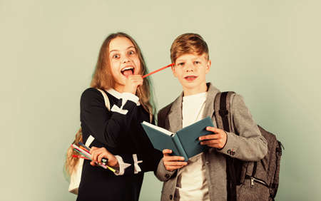 Vacations over, school is here. Little children back to school. Small boy and girl hold pens and textbook. School time. Private lesson. Education and study. September 1. Knowledge day