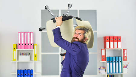Stress concept. Crazy or mad. Business man aggressive. Hipster man angry with office chair. Throw out chair. Imagens