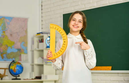 Small child holding ruler for mathematics lesson. Science and Technology. Cute little schoolgirl with geometrical tool for mathematics. Elementary school mathematics or maths. Mathematics matters