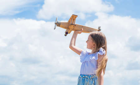 Travel by plane. Keep dreaming. kid play wooden toy airplane. Study geography. Dreams about travel. Story about summer vacation. small girl hold wooden plane. imagination