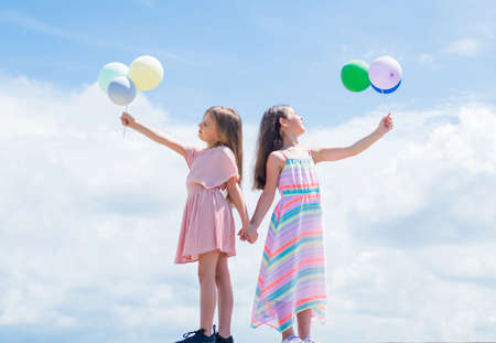 happy childhood. summer vacation. small girls embrace. love and support. concept of sisterhood and friendship. family bonding time. best friends with balloon. two sisters hold party balloon