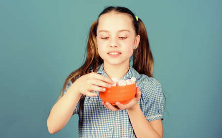 Who cares about diet. Sweet and soft. Sweet tooth concept. Calorie and diet. Girl smiling face hold bowl sweet marshmallows in hand blue background. Kid girl with long hair likes sweets and treats