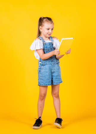 small girl hold notebook. read the book. ready for reading. lesson of literature. happy childhood. back to school. development of smart kids. express interest and intelligence Stok Fotoğraf