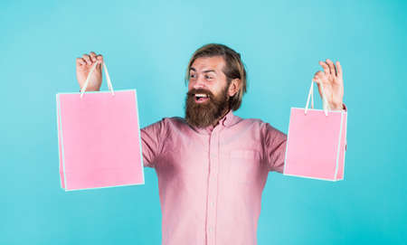 Thanks for your purchase. surprised male open shopping bag with something exciting inside. mature man casual in surprise with present package. commonly used for birthday. buy anniversary gifts