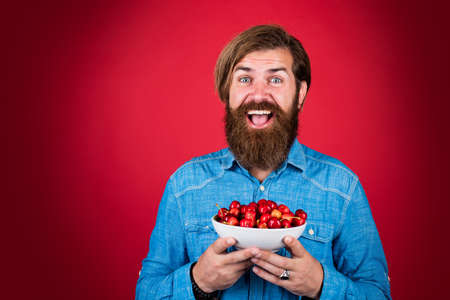 happy bearded man with sweet cherry. cherries for breakfast. cheerful male hipster hold fresh berry. fruit full of vitamin. only organic food. dieting and healthy lifestyle