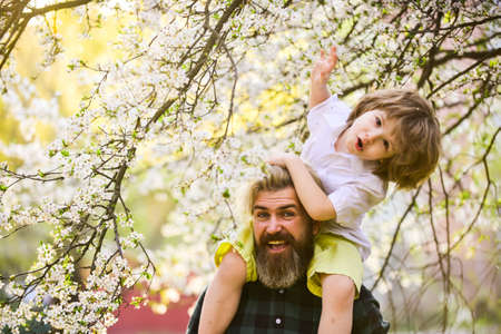 Springtime. Hipster piggybacking baby. Bearded brutal man good father. Dad and son. Best dad ever. Fathers day. Child having fun with dad. Happy family. Little boy and father in nature background