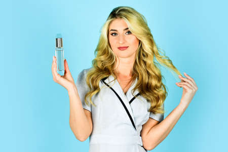 long lasting scent. fresh and unique fragrance. woman perfume in hand. blond girl with curly hair. hair oil spray. beauty and fashion. shop assistant offer natural cosmetics. female perfume Stock Photo