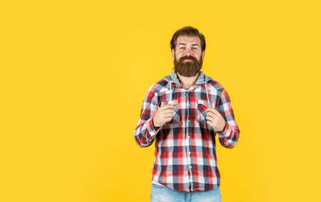 Confident and handsome brutal man. copy space. portrait of handsome bearded man in plaid shirt. man wearing casual clothes. brutal happy man with beard standing indoor. Young and brutal 版權商用圖片