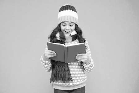 Interesting information. Library concept. Reading skills. Winter story. Girl reading book. Kid enjoying book. Little book lover. My favorite story. Leisure in winter time. Childhood development Stock Photo