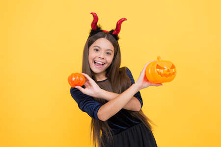 a real treat. halloween devil girl. happy childhood. teenage child in imp horns. cheerful kid hold creepy pumpkin. carnival costume party. trick or treat. celebrate the holidays. jack o lantern