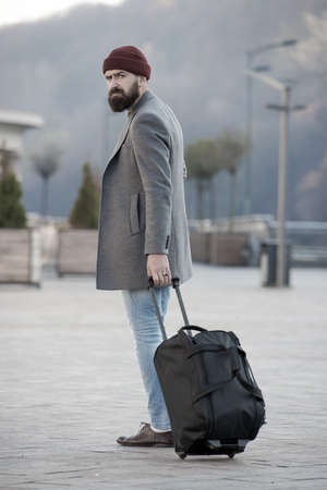 Carry travel bag. Man bearded hipster travel with luggage bag on wheels. Adjust living in new city. Traveler with suitcase arrive airport railway station urban background. Hipster ready enjoy travel