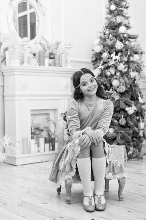 Dreams come true. Hope concept. Dreamy baby christmas wish. Making wish. Waiting for Santa claus. Adorable girl making wish near christmas tree decorated interior. Hopeful child. New year eve