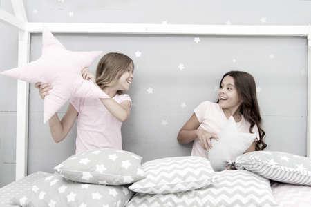 Girls sleepover party ideas. Soulmates girls having fun sleepover party. Girls happy best friends in pajamas with pillows sleepover party. Pillow fight pajama party. Sleepover time for pillow fight Stock Photo