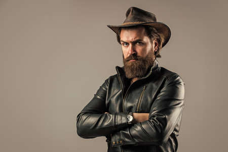 Cowboy couture. modern west lifestyle. serious brutal bearded man. handsome and successful man in cowboy hat. He is in leather jacket. stylish successful man biker. western man wear leather Banque d'images