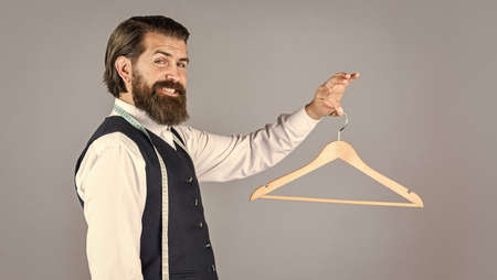 portrait of man holding hanger. tailor man use tape measure. professional male sartor with measuring tape and hanger. Handsome man in smart casual wear is holding hanger Standard-Bild