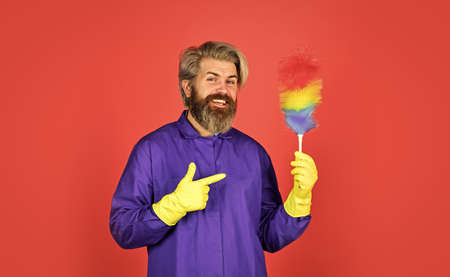 Cleaning service. Housekeeping duties. Cleaning apartment. Man use pp duster. Dust allergy. Polypropylene duster. Hipster holding cleaning tool. Cleaning home concept. Small colorful duster broom