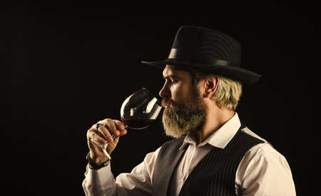 alcohol beverage. Elegant waiter drink red wine. working in wine cellar. bar or winery. wine degustation. Bearded businessman in elegant suit with glass of wine. Sommelier tastes expensive drink