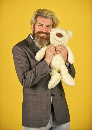 Friend and friendship. Adoption and adoptive parent. Friendly relations. Imaginary friend. Still childish in soul. Happy businessman hug teddy bear yellow background. Bearded man with toy friend Foto de archivo