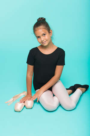 Child tender dancer look gorgeous fancy leotard. Dream every girl become famous gymnast. Kid sit hold pointe ballet shoes. Special shoes for ballet. Child flexible gymnast practice stretching tiptoes Stock Photo