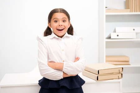 Just heard excellent news. Child girl wears school uniform standing excited face expression. Schoolgirl smart child looks excited white interior background. Girl remember pleasant memory childhood