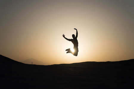 Achieve main goal. Silhouette man motion jump in front of sunset sky background. Future success depends on your efforts now. Daily motivation. Healthy lifestyle personal achievement goal and success