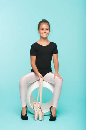 Child flexible gymnast practice stretching tiptoes. Child tender dancer look gorgeous fancy leotard. Dream every girl become famous gymnast. Kid sit hold pointe ballet shoes. Special shoes for ballet
