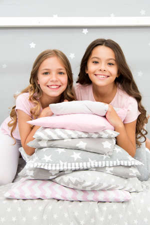 Girls best friends gather in bedroom for slumber party. Domestic party for kids. Girls near pile pillows posing with brilliant smiles. Lets start this party. Kids in pajamas prepare bedroom for party