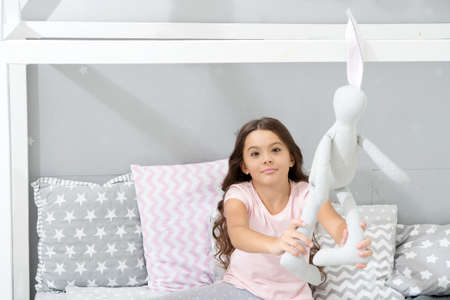 Play soft toy before go sleep. Girl long curly hair enjoy evening time with favorite toy. Kid sit bed and play bunny toy modern bedroom interior. Evening time. Girl child wear pajamas play bunny toy