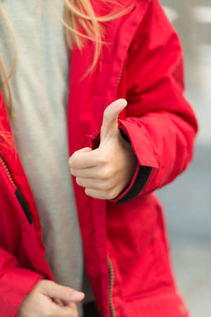 Hand of baby shows thumbs up gesture. Kid wear warm jacket show gesture of approvement or accept. She likes this. Thumb up gesture meaning like and agreement. Thumbs up and like concept