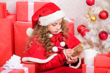 Wish list. Child santa costume enjoy christmas eve. Child write letter to santa claus. Dear santa. Girl hold pen and paper near christmas tree and gift box. Believe in miracle. Send letter for santa Stock Photo