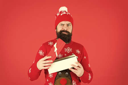 Handsome man celebrate winter holidays red background. Christmas shopping. Secret Santa could ease holiday stress. Merry christmas and happy new year. Christmas present concept. Guy wear winter hat Standard-Bild