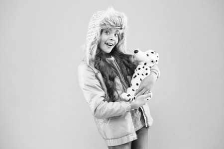 i love pets. small girl care dog toy. pet care concept. little child warm puffer jacket. fashionable kid earflap hat. winter fashion. childhood dream. friendship between animal and human. Be Nice