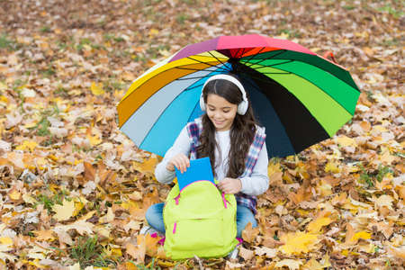 going to read the book. happy childhood. back to school. girl in headset with backpack relax in park. enjoy fall in forest. listen to music. online courses education. autumn kid under umbrella
