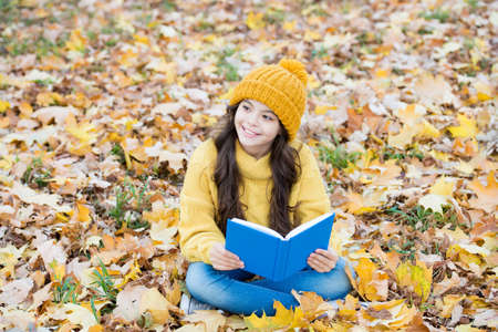 Read readily. Happy child read book sitting on autumn leaves. School library. Literacy education. Literature lesson. Reading forever