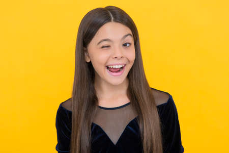 Happy little girl child smile winking with open mouth and showing healthy teeth yellow background, dentistry