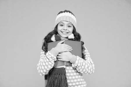 love it so much. kid enjoying her book. winter story reading. christmas eve. little book lover. cosy and comfort. my favorite story. leisure in winter time. childhood development. Girl reading book Stock Photo
