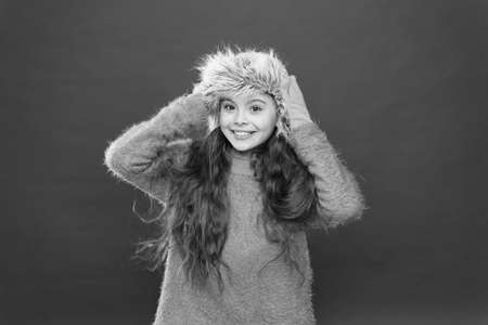 Small fashionista concept. Feeling so cozy. Child long hair soft hat. Winter fashion concept. Warm hat for cold winter weather. Kid girl smile red background. Soft furry accessory. Winter season Archivio Fotografico