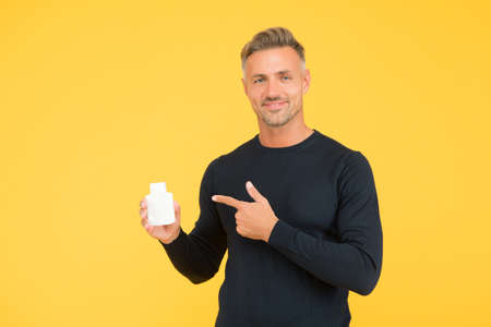 Styling your hair should be simple. Happy man point finger at bottle yellow background. Shampooing and conditioning. Hair salon. Barbershop. Mens grooming. Haircare should be your first priority