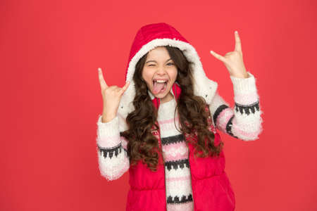 happy teen girl with long curly hair wear puffer waistcoat and sweater with christmas patterns, winter style