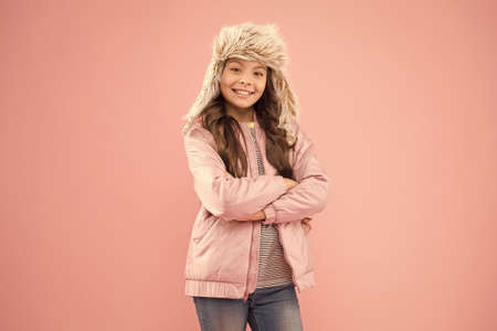 Christmas vacation. warm clothes for cold season. fur earflap hat accessory. small girl winter hat. autumn style. Childhood activity. kid fashion. girl look like hipster. happy child pink background