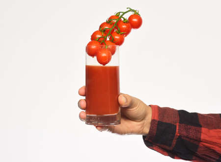 Male hand holds glass of tomato juice with berries inside