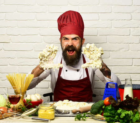 Chef kneads dough. Man with beard and hands in dough Foto de archivo