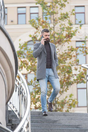 Hipster talk on mobile phone coming down stairs urban outdoors