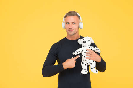 Its more then a toy. Handsome man point finger at toy dog. Toyshop. Play and game. Imaginative activity. Learning fun together