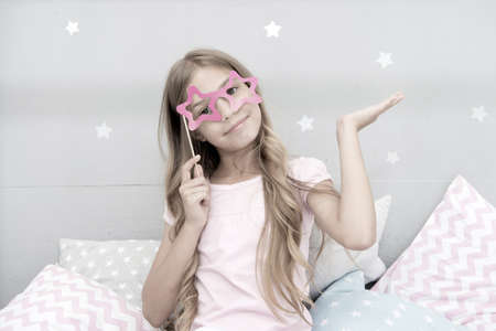 I am super star. Girl with long blonde curly hair posing photo booth props. Pajamas party concept. Girl star shaped eyeglasses at pajamas party. Cheerful young lady posing with eyeglasses Imagens