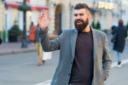 Hipster in casual coat happy to meet friend at urban street. Chance meeting concept. Meet old friend by accident. Man bearded businessman waiting someone in city center. Happy to meet you