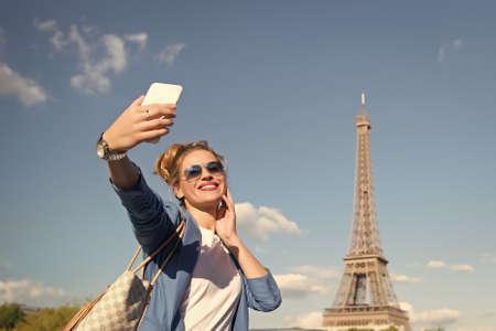girl making selfie front of Eiffel Tower in Paris, France.