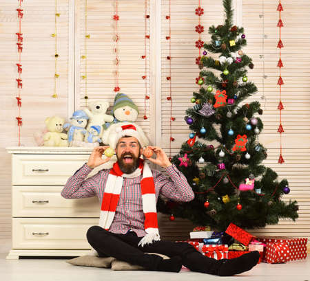 Man with beard in hat and scarf holds Christmas balls